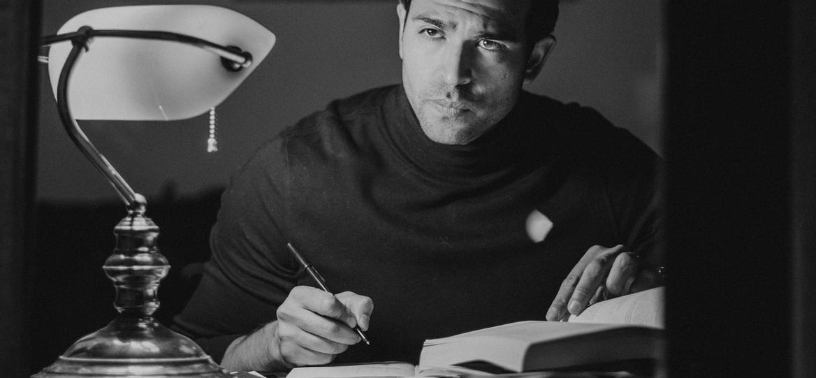 man writing under a lamp