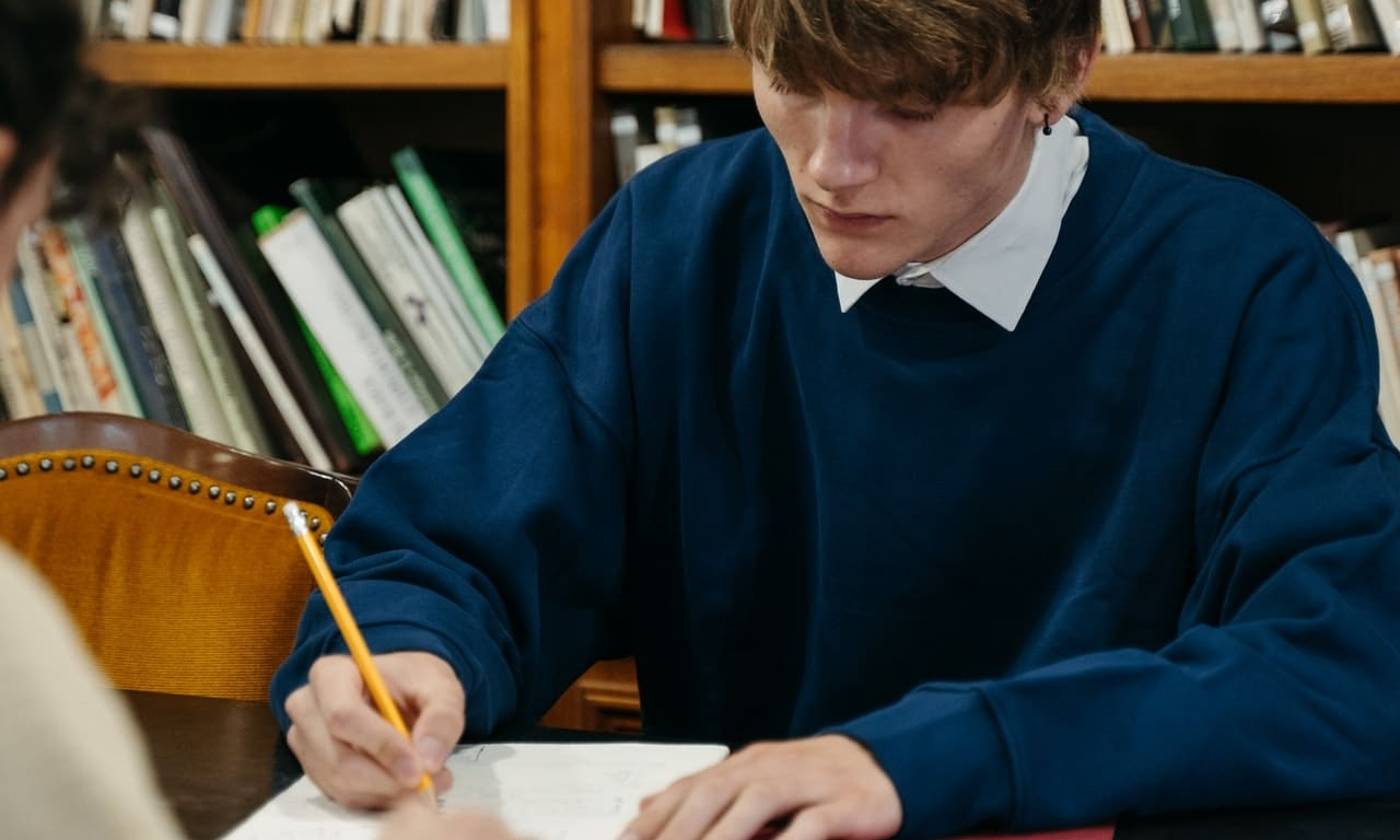 boy writing and studying
