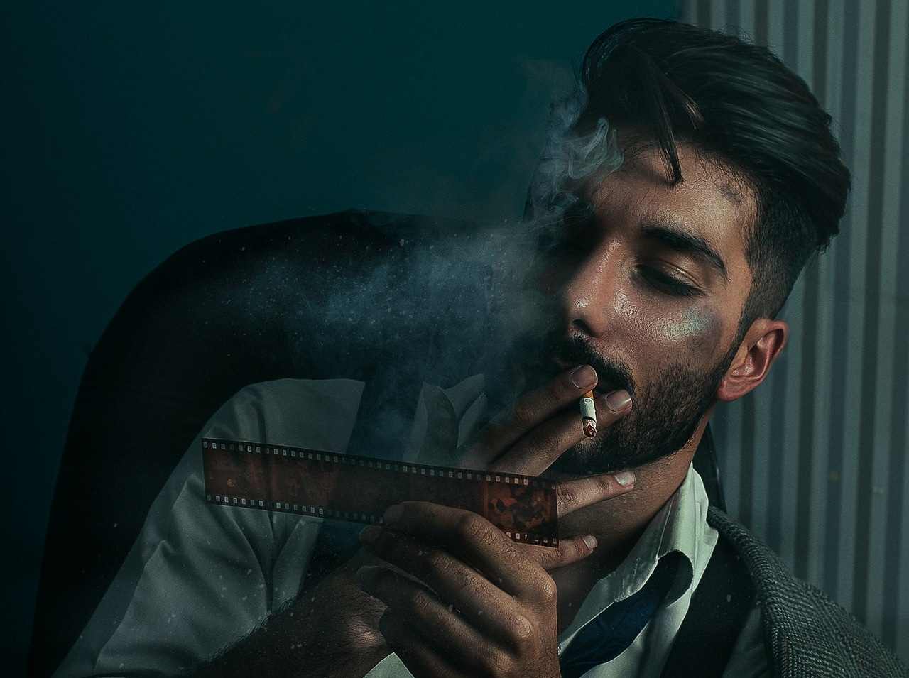man smoking a cigarette while looking at a film
