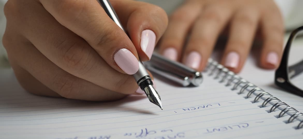 person writing on a piece of paper