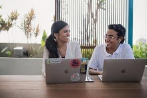 deux personnes travaillent ensemble et sourient