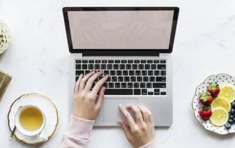 femme sur son ordinateur avec une assiette de fruits et un thé