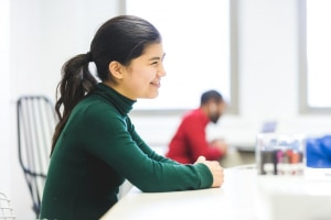 fille sourinate assise au bureau de sa classe