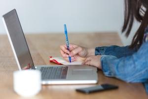 fille travaille avec son ordinateur et écrit dans un cahier