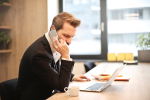 man-talking-on-the-phone-at-his-desk