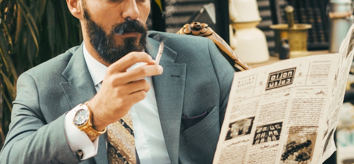 bearded man smoking and reading the newspaper