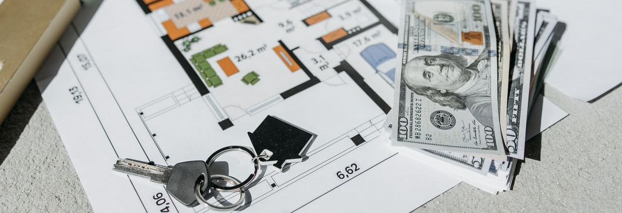 house keys and money on an architecture plan